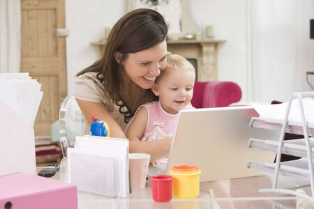 looking for work: Mother and  in home office with laptop Stock Photo