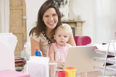 after to work: Madre y beb� en la oficina en casa con ordenador port�til