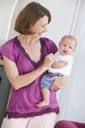 12 month old: Madre nel soggiorno azienda bambino sorridente