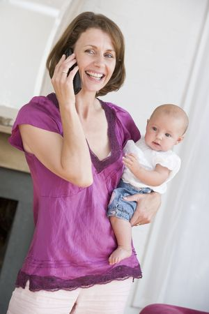 Mother in living room using telephone holding baby smiling photo