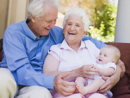 Grandparents outdoors on patio with baby smiling photo