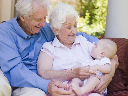abuelos: Abuelos en el patio al aire libre con el beb� sonriendo Foto de archivo