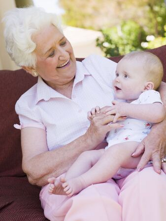 grandma: Grandmother outdoors on patio with baby smiling Stock Photo