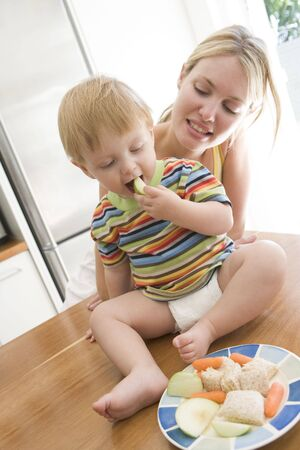 twenty four month old: Mother and  in kitchen eating fruit and vegetables
