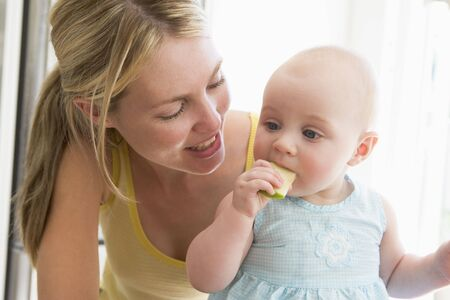Mother and baby in kitchen eating apple photo