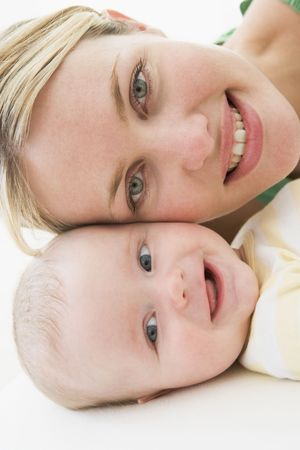 Mother and baby lying on floor smiling photo