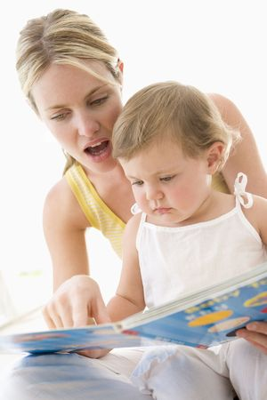 infant girl: Mother and  reading book indoors and pointing Stock Photo