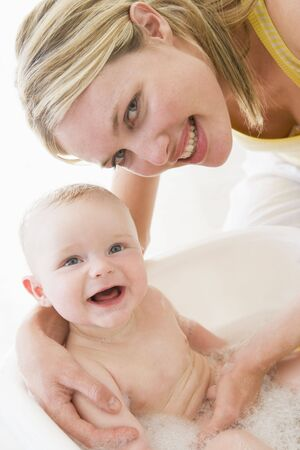 Mother giving baby bubble bath smiling photo