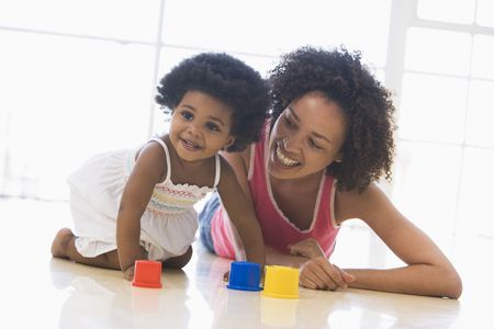 Mother and daughter indoors playing and smiling photo