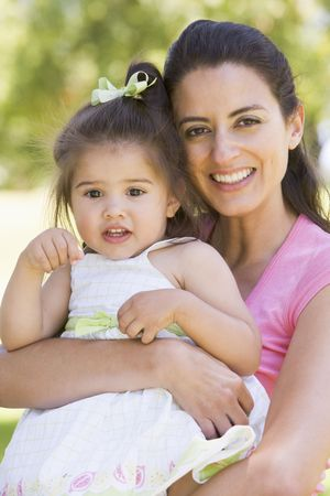 twenty four month old: Mother holding daughter outdoors smiling