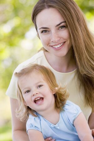 24 month old: Mother holding daughter outdoors smiling