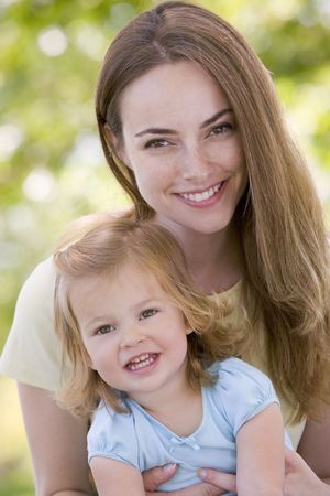 countryside loving: Mother holding daughter outdoors smiling