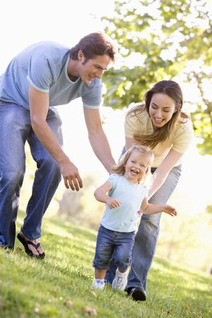 twenty four month old: Family running outdoors smiling Stock Photo