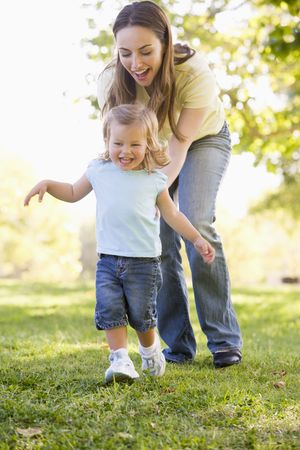 twenty four month old: Mother and daughter playing outdoors smiling Stock Photo