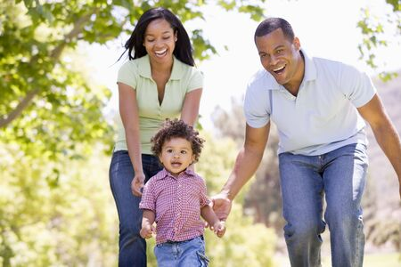 24 month old: Family running outdoors smiling Stock Photo