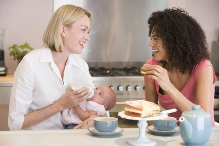 Mother and  in kitchen with friend eating cake and smiling photo