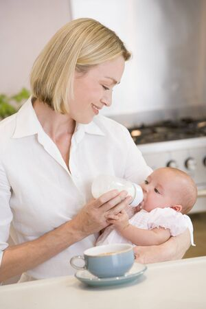 Mother feeding baby in kitchen with coffee smiling photo