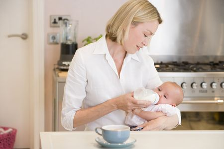 Mother feeding baby in kitchen with coffee photo