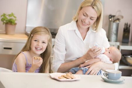 Mother feeding baby in kitchen with daughter eating cookies and smiling photo