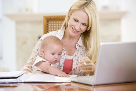 Mother and baby in dining room with laptop smiling photo