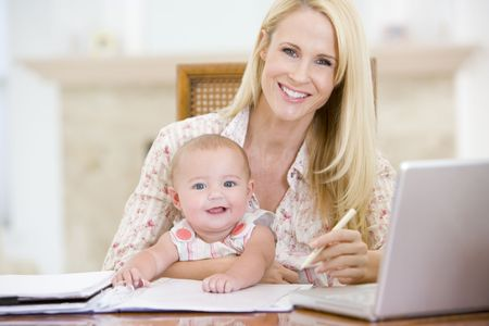Mother and baby in dining room with laptop smiling Stock Photo - 3600607