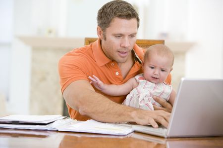 x files: Father and baby in dining room with laptop Stock Photo