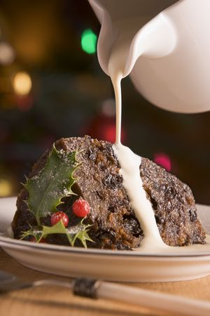 pudding: Portion of Christmas Pudding with Pouring Cream Stock Photo