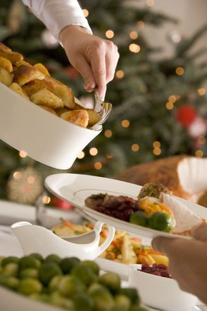 festive food: Serving Roast Potatoes at Christmas Lunch Stock Photo