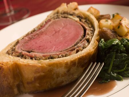 entre: Slice of Beef Wellington with Spinach and Saut ed Potatoes Stock Photo