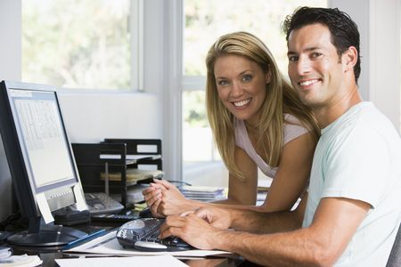 home office desk: Couple in home office with computer smiling Stock Photo