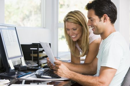 home office desk: Couple in home office with computer and paperwork smiling
