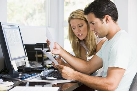 Couple in home office with computer and paperwork looking unhappy photo
