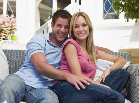 Couple sitting outdoors on patio smiling photo