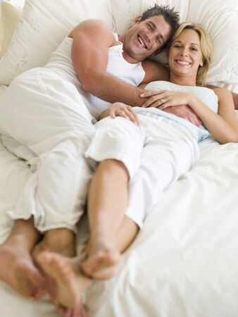 cuddling: Couple lying in bed smiling