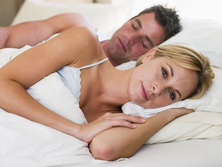 day bed: Couple lying in bed with the man sleeping Stock Photo