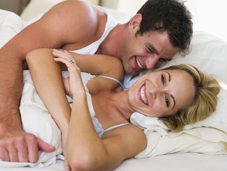 awaken: Couple lying in bed laughing Stock Photo