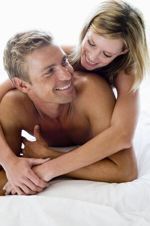 couple cuddling: Couple lying in bed smiling