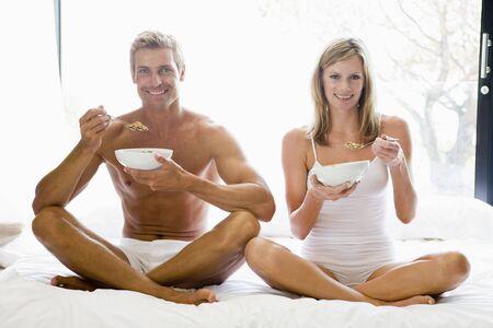 comiendo cereal: Pareja sentada en la cama comiendo cereales y sonriente Foto de archivo