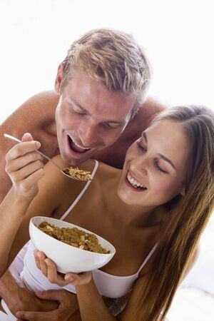 Couple sitting in bedroom eating cereal and smiling photo