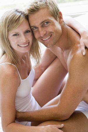 couple cuddling: Couple in bedroom embracing and smiling Stock Photo