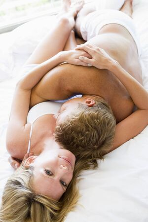 couple cuddling: Couple lying in bed embracing and smiling