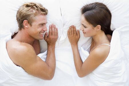 sexy woman on bed: Couple lying in bed smiling