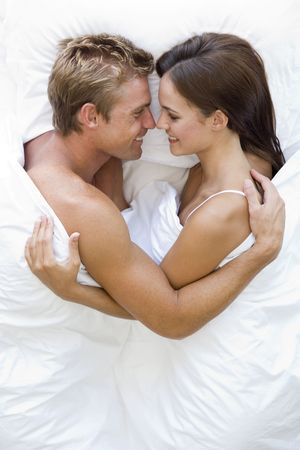 sexy young couple: Couple lying in bed smiling