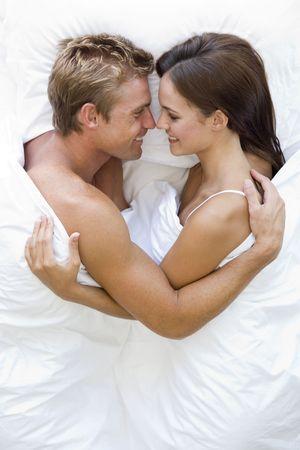 pareja en casa: Joven en la cama sonriente
