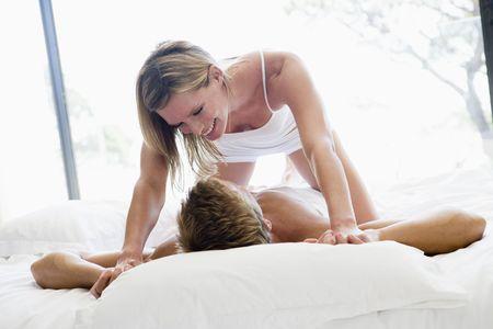 pareja en la cama: Pareja en la cama est� juguet�n y sonriente