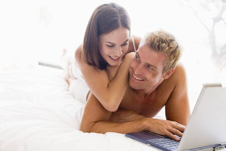 Couple lying in bed with laptop smiling photo