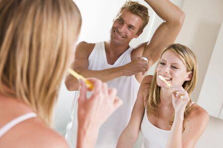 Couple in bathroom brushing teeth and applying deodorant photo