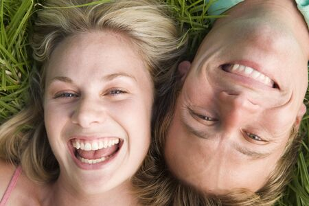Couple lying in grass smiling photo