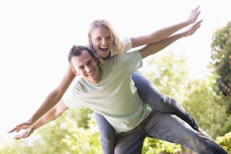 Man giving woman piggyback ride outdoors smiling photo
