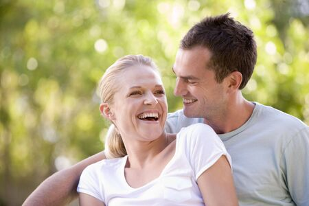 Couple sitting outdoors laughing Stock Photo - 3601478